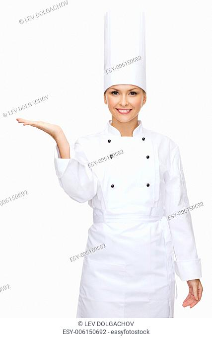 cooking, advertisement and food concept - smiling female chef holding something on palm of hand