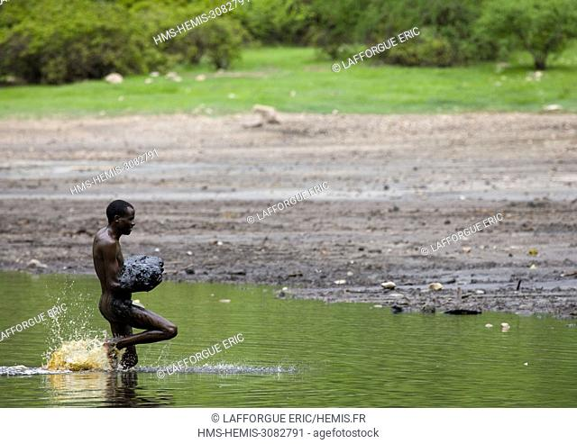 Ethiopia, Oromia, El Sod, Borana tribe man getting out of the crater lake of el sod volcano with volcanic mud in the arms