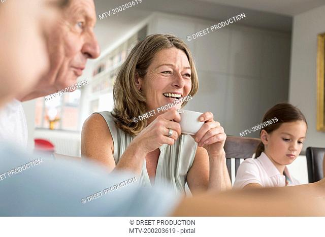 Smiling mature woman with cup of coffee surrounded by family