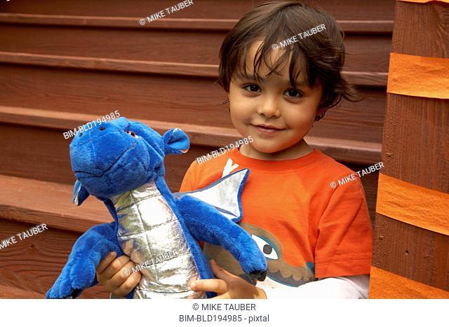 Mixed race boy holding stuffed dragon