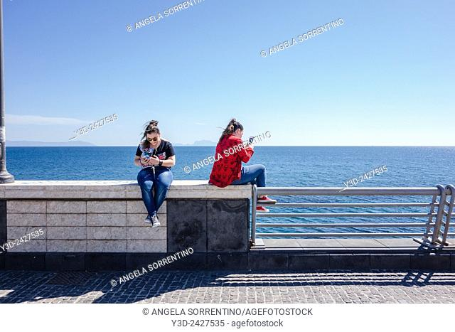 Two girls using smartphone on the sea promenade, Naples, Italy