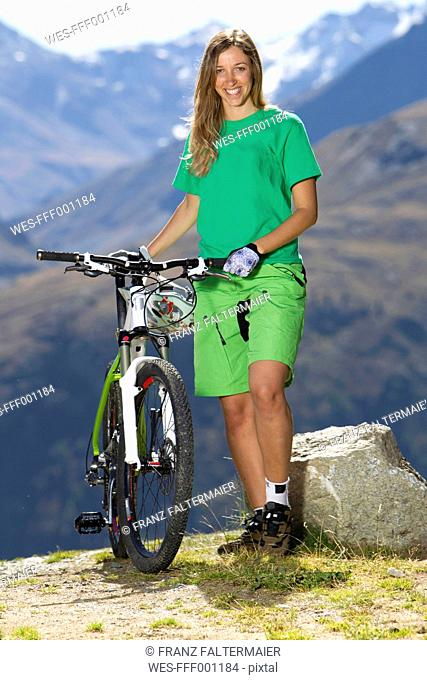 Italy, Livigno, View of woman standing with mountain bike