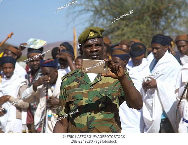 Soldier filming with his mobile phone during the Gada system ceremony in Borana tribe, Oromia, Yabelo, Ethiopia
