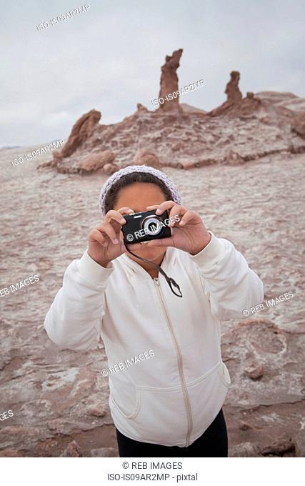 Young girl taking photograph using camera, Valley of the Moon, San Pedro, Atacama, Chile