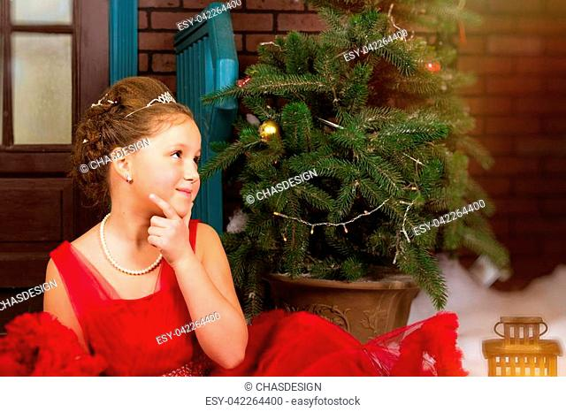 Cute little teenage girl in red dress welcomes New year and Christmas in enchanting holiday interior with decorated Christmas tree and artificial snow