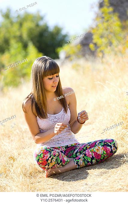 Teen-girl in colorful pants in nature sitting crossed-legs