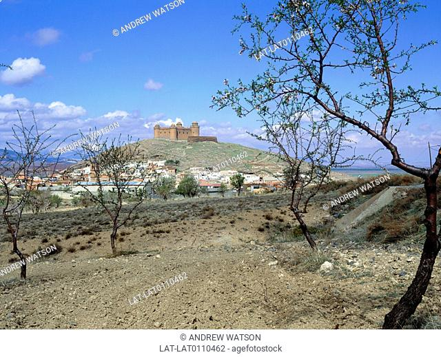 Near Granada. Village,houses. Hilltop castle built by Christians against the Moors. Foothills,Sierra Nevada chain