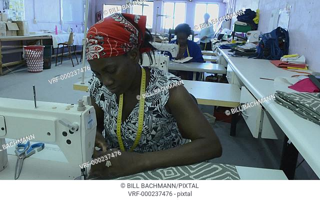 Windhoek Namibia Africa woman sewing fabrics and crafts at Penduka Craft Center for sale to tourists