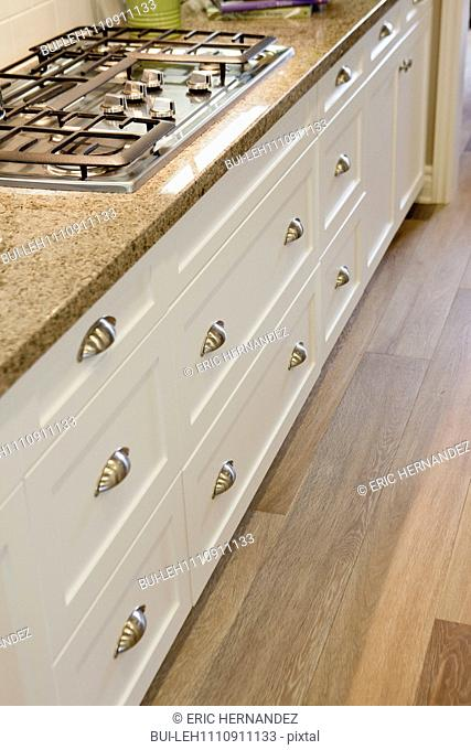 Close-up of gas stove with white cabinets and hardwood floor in kitchen at home