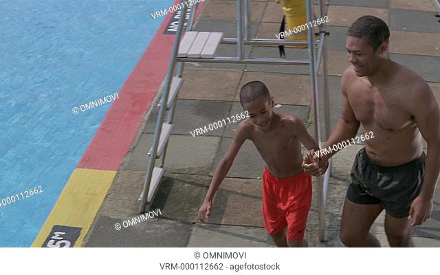 Father and son walking hand in hand and jumpping to pool