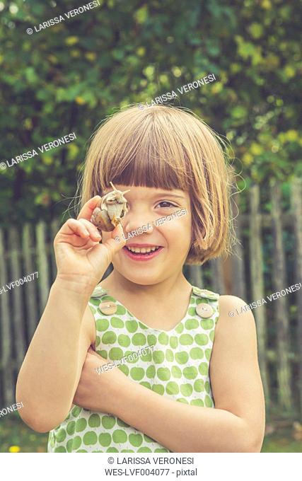 Portrait of smiling little girl holding vineyard snail