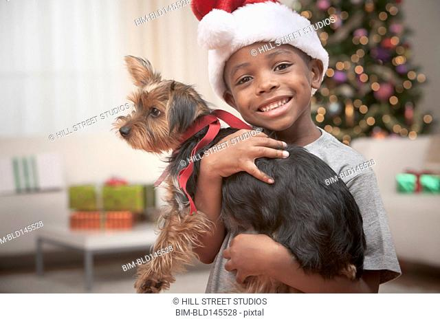 Happy Black boy in Santa hat holding small dog