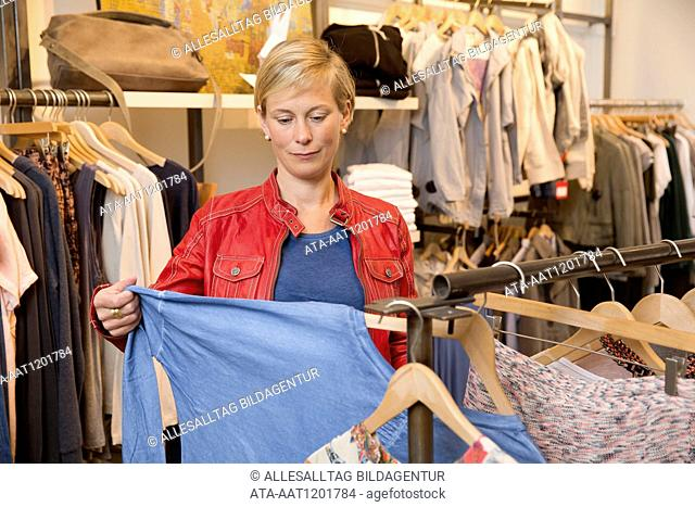 Woman is looking for clothes in a boutique
