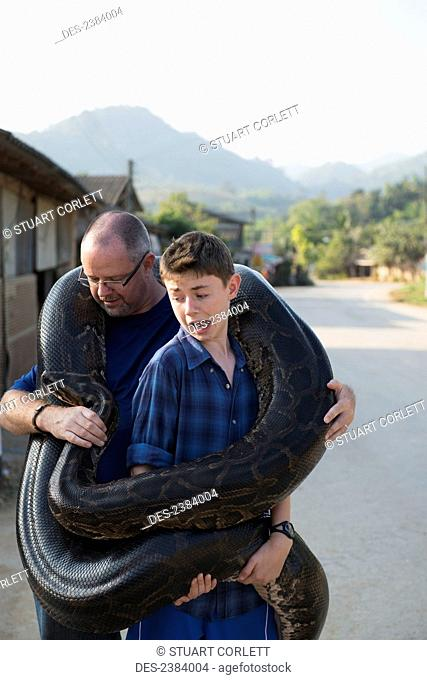 Father and son holding a very large python; Thaton, Chiang Rai, Thailand
