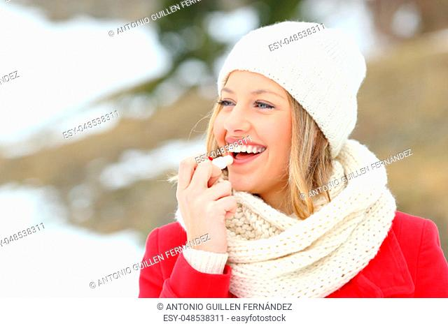 Girl protecting lips with lip balm in winter with a snowy mountain in the background