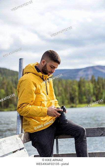 Finland, Lapland, young man with a camera on jetty at a lake