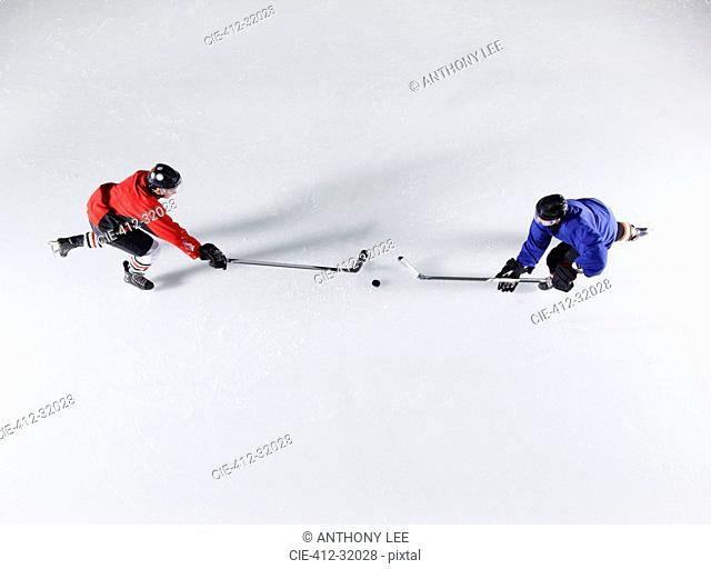 Overhead view hockey opponents going for the puck on ice