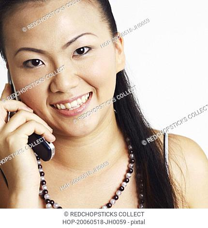 Portrait of a young woman smiling and talking on a mobile phone
