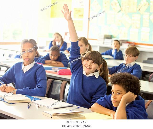 Elementary school children in classroom during lesson, smiling girl raising hand