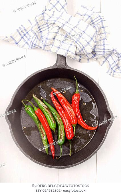 grilled green and red chili in a cast iron pan