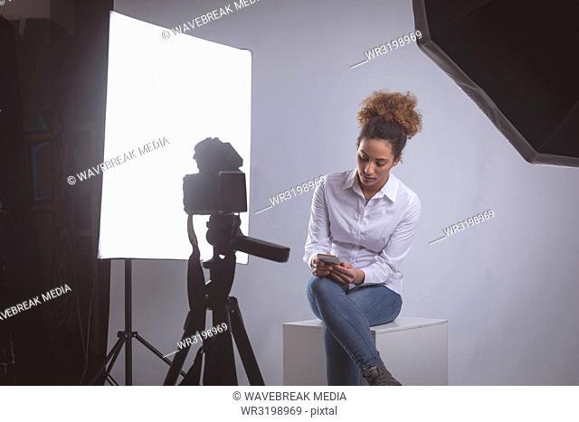 Female photographer using mobile phone