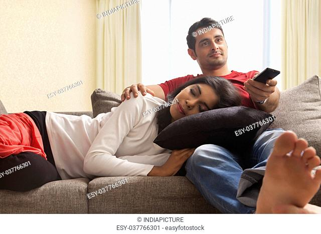 Man watching television, woman sleeping on man's lap