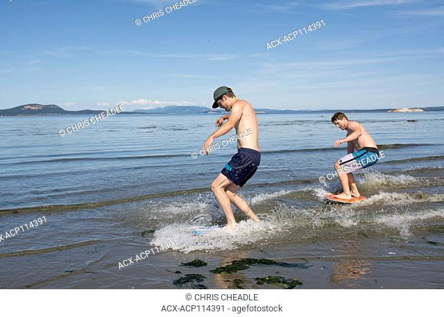 Young men skim boarding on the beach at Sidney Island, British Columbia, Canada