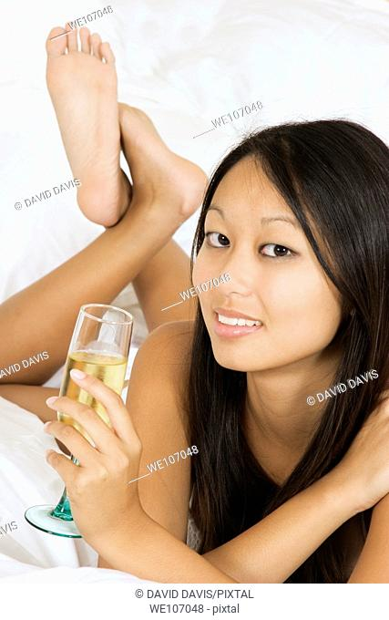 Asian woman in early 20's laying in bed holding a glass of white wine