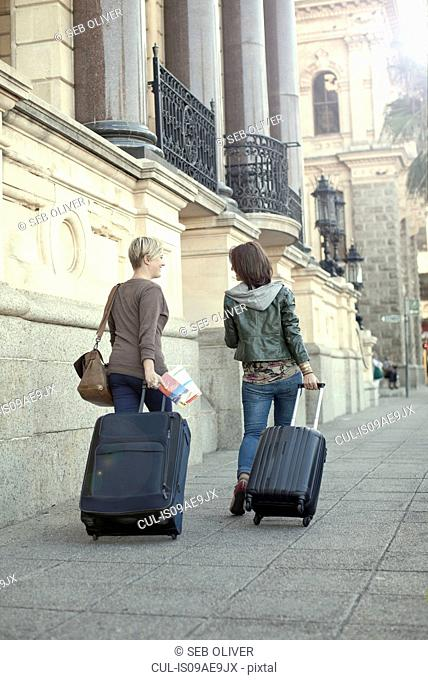 Two female friends pulling suitcases on sidewalk, Cape Town, South Africa