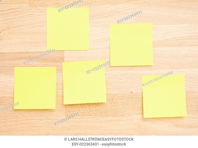 Empty sticky notes on wooden table. Office desktop background with copy space