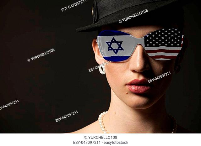 Portrait of woman with USA and Israel flag sunglasses on black background