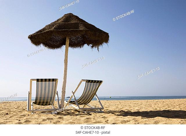 Two sun loungers and sunshade on the beach, Tunisia