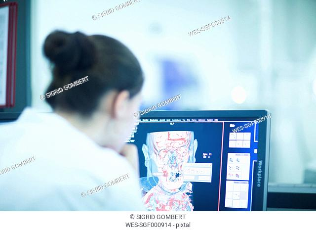 Young doctor in hospital looking at computer screen