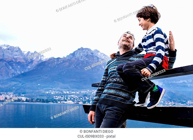 Boy and father sitting on pier fence, Lake Como. Onno, Lombardy, Italy