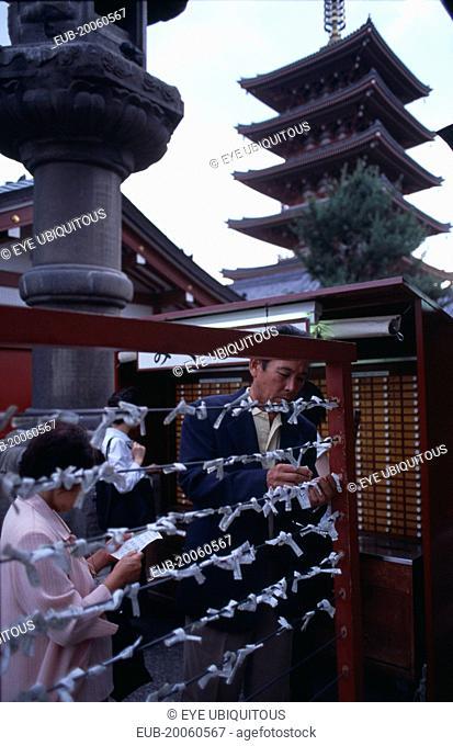 Asakusa. People tying Omikuji or Fortune papers at Senso Ji Temple