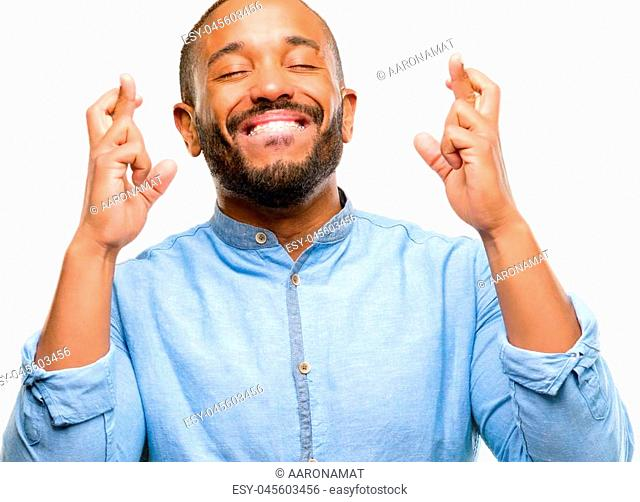 African american man with beard with crossed fingers asking for good luck isolated over white background