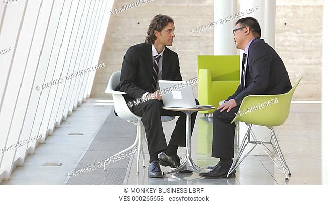 Two Businessmen sit at table in modern office looking at laptop together.Shot on Canon 5d Mk2 with a frame rate of 30fps