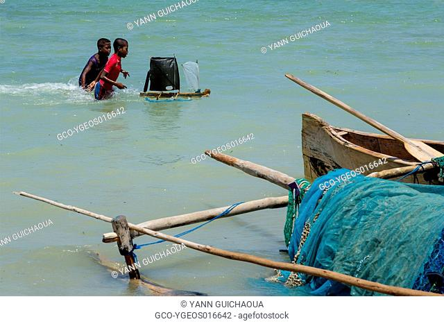 Young people playing with a pirogue model,Fishing harbour at Ifaty, near Tulear, Madagascar
