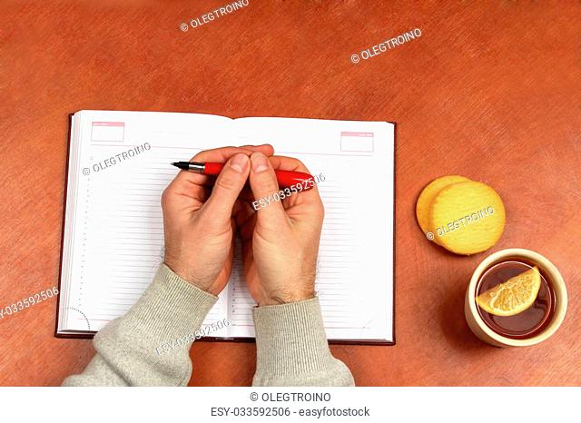 two hands with red pen lying on a notebook on office Desk with tea and biscuits