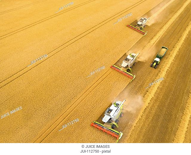 Aerial view of combine harvesters in golden barley field