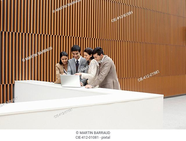 Business people using laptop at ledge in office