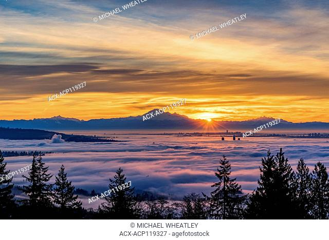 A temperature inversion causes clouds of fog to blanket Vancouver and the Lower Mainland, British Columbia, Canada