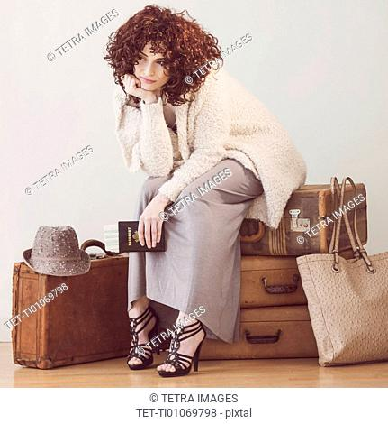 Beautiful brunette woman sitting on suitcases
