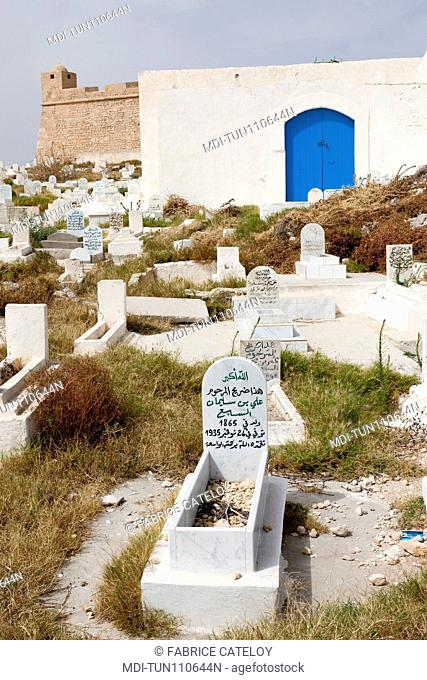 Tunisia - Madhia - Tombs in the cemetery and in the background the fort