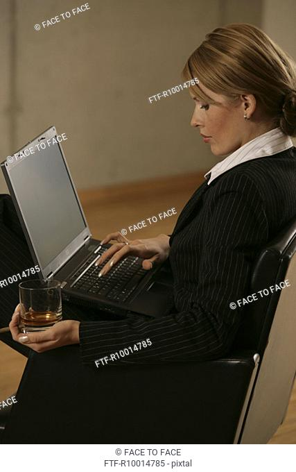 A blonde businesswoman smoking and drinking with a laptop on her lap