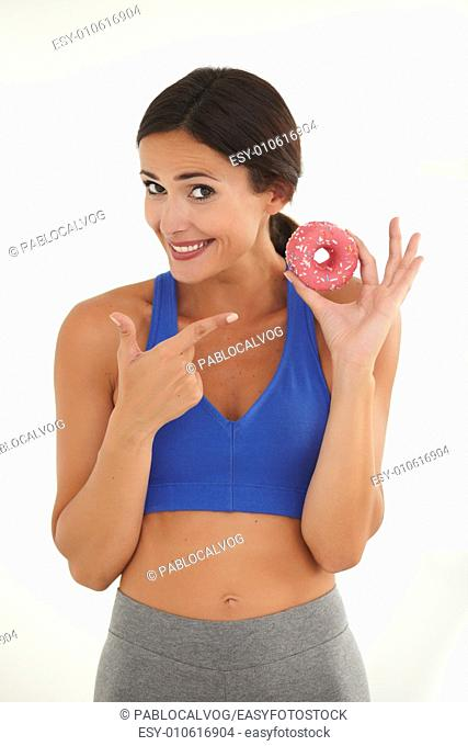 Hispanic fit female in sports clothing pointing at cake