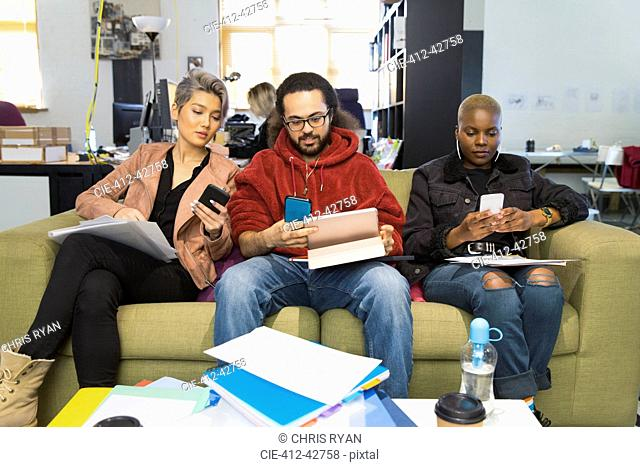 Creative business people using smart phones, meeting in casual office