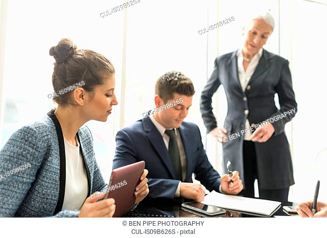 Businessman and women making notes in boardroom meeting