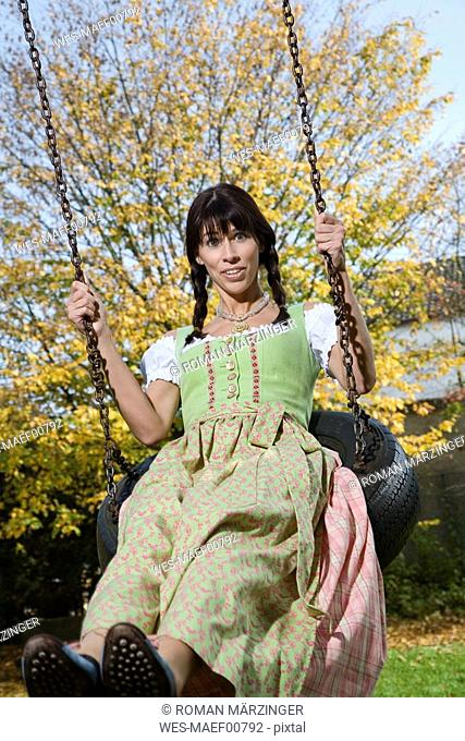 Brunette woman in dirndl dress, swinging, portrait