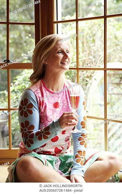 Mature woman holding a champagne flute and smiling